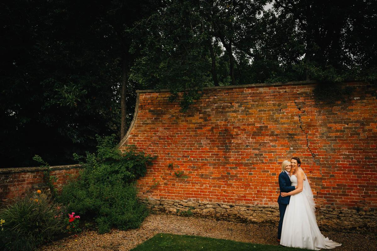 two brides hug in the gardens at Arnos Vale wedding venue in Bristol