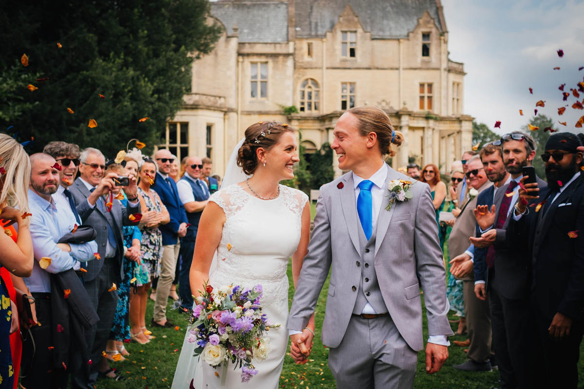 bride and groom walk down an aisle of wedding guests as they throw confetti over them at their Manor House at Old Down Estate wedding
