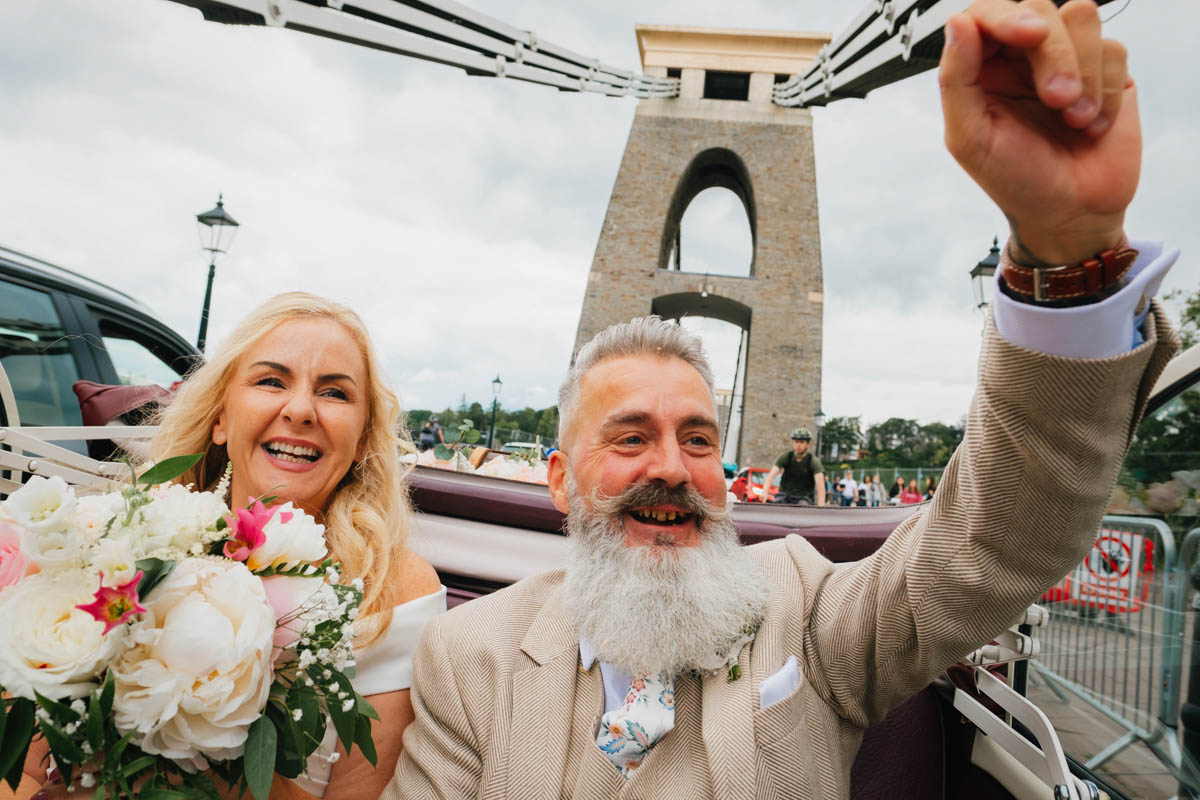 groom waves his hands in the air in the back of an open-top vintage car with his wife next to him as they drive over Clifton suspension bridge