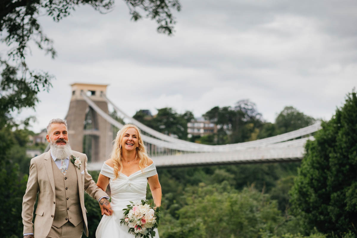 bride and groom holding hands walking in front of the bristol suspension bridge in Clifton